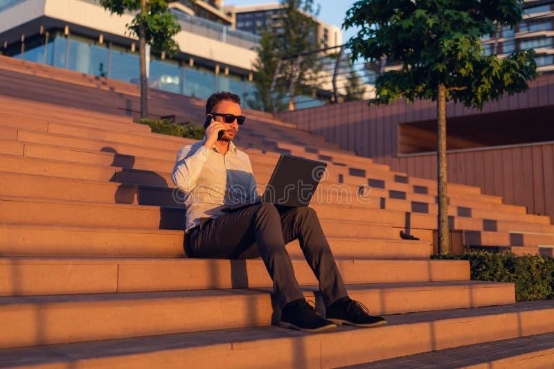 Stående av den lyckade affärspersonen med bärbara datorn och smartphonen som utomhus sitter på trappa fotografering för bildbyråer