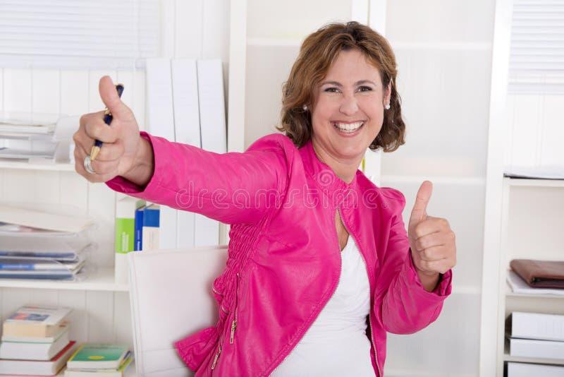 Stående av den lyckade attraktiva affärskvinnan med tummar upp. royaltyfria bilder