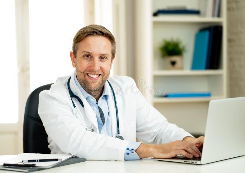 Stående av den lyckade specialistdoktorn som arbetar i sjukhuskontoret som ser lyckligt och säkert royaltyfria bilder