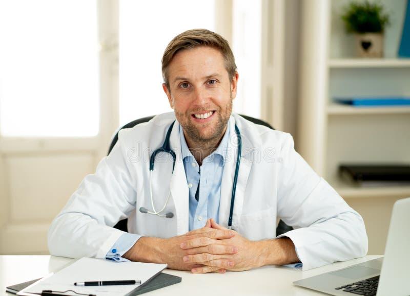 Stående av den lyckade specialistdoktorn som arbetar i sjukhuskontoret som ser lyckligt och säkert royaltyfri bild