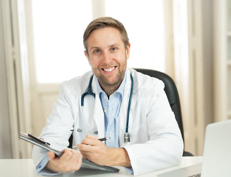 Stående av den lyckade specialistdoktorn som arbetar i sjukhuskontoret som ser lyckligt och säkert fotografering för bildbyråer