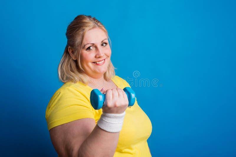 Stående av den lyckliga överviktiga kvinnan med hanteln i studio på en blå bakgrund arkivfoto