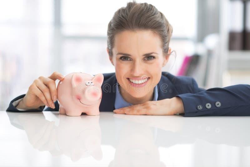Stående av den lyckliga affärskvinnan med spargrisen arkivbild