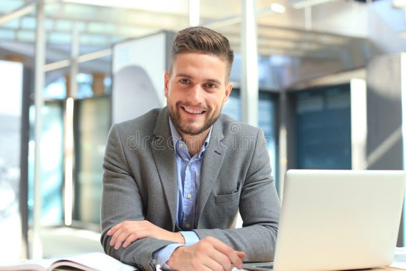Stående av den lyckliga affärsmannen som sitter på kontorsskrivbordet och att se kameran som ler royaltyfri bild