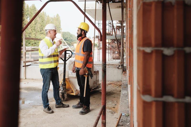 Stående av den lyckliga arbetsledaren för konstruktionsplats som talar till den manuella arbetaren arkivfoto