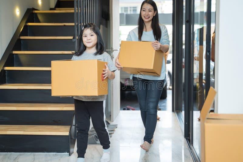 Stående av den lyckliga asiatiska familjen som flyttar sig till det nya huset med kartonger fotografering för bildbyråer