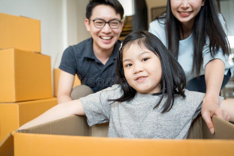 Stående av den lyckliga asiatiska familjen som flyttar sig till det nya huset med kartonger och spelar kartongen arkivfoto