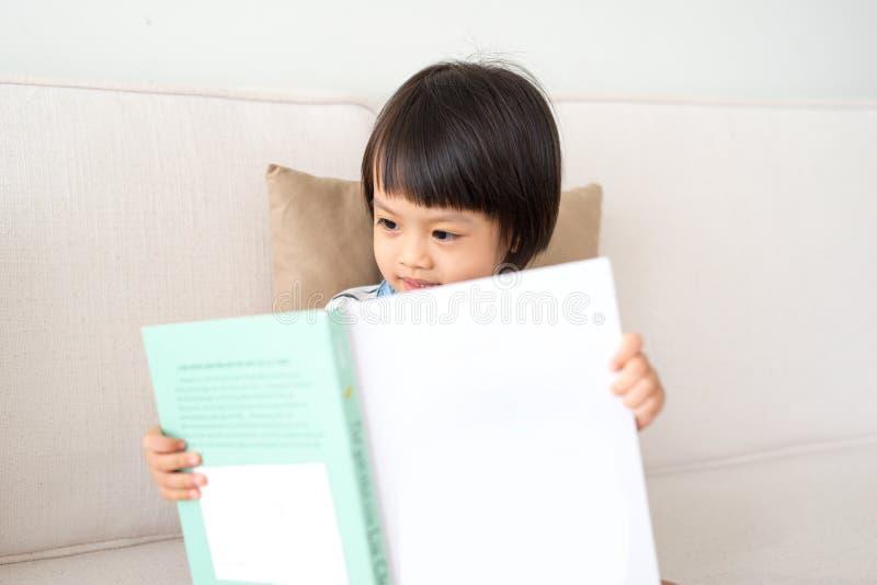 Stående av den lyckliga asiatiska flickaläseboken för litet barn arkivfoton