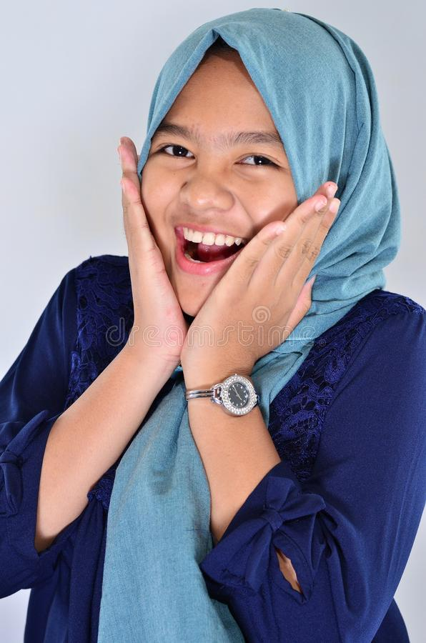 Stående av den lyckliga asiatiska flickan som bär blå hijab som ler på dig och trycker på hennes kind royaltyfria foton