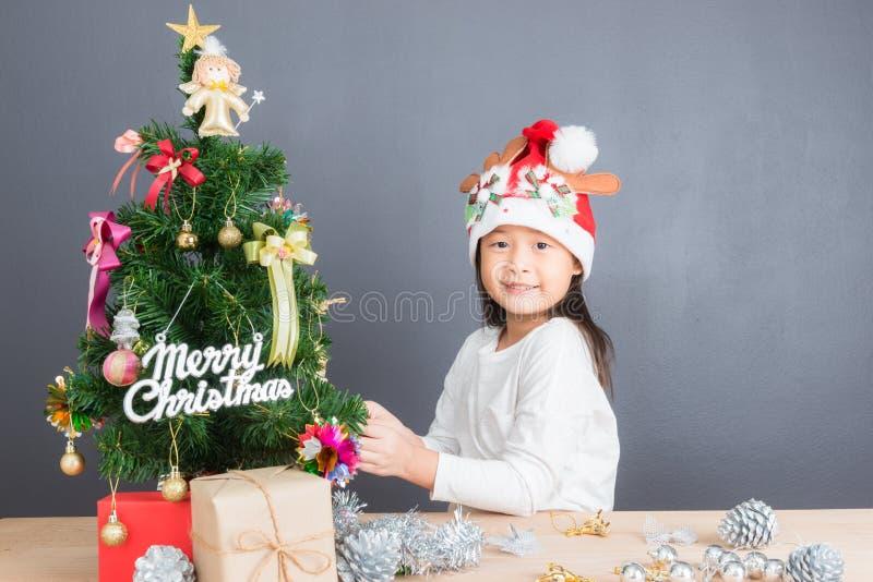 Stående av den lyckliga asiatiska flickan som dekorerar den lilla julgranen arkivfoton