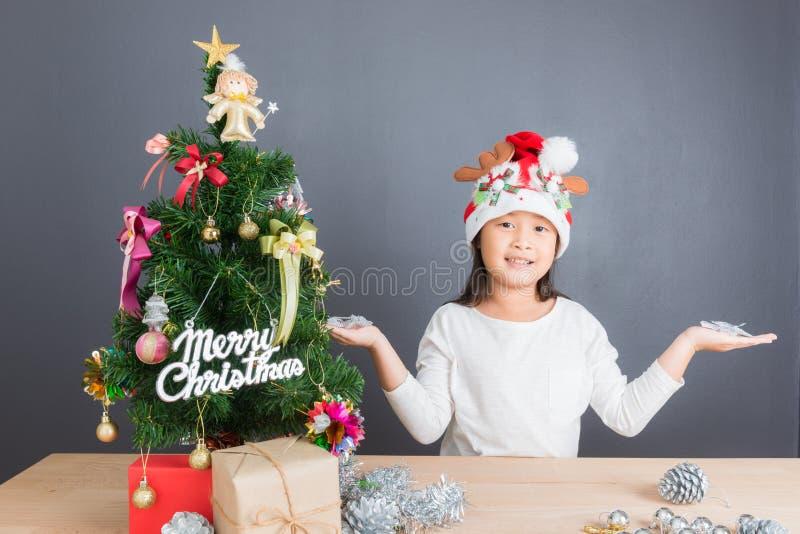 Stående av den lyckliga asiatiska flickan som dekorerar den lilla julgranen royaltyfri bild