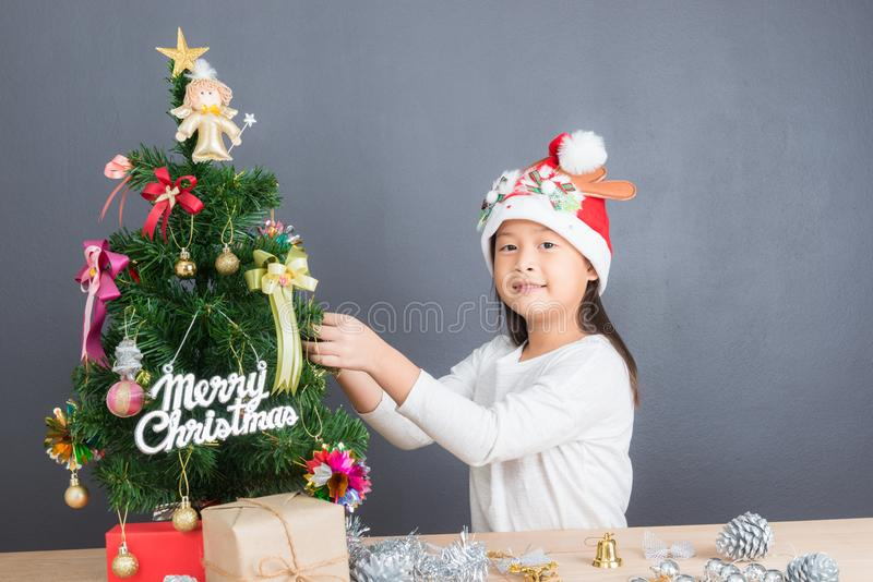 Stående av den lyckliga asiatiska flickan som dekorerar den lilla julgranen arkivbild