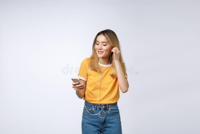 Stående av den lyckliga asiatiska unga kvinnan att lyssna till musik med headphonen fotografering för bildbyråer