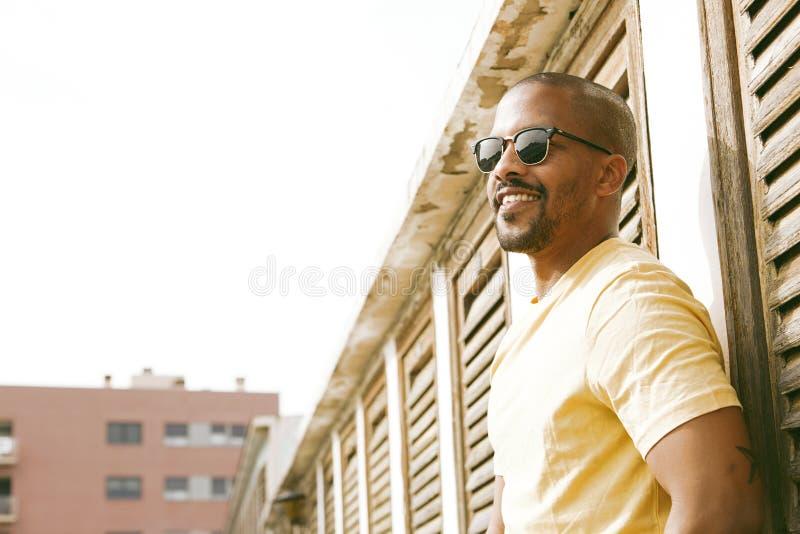 Stående av den lyckliga attraktiva unga afrikansk amerikanhipsteren i t-skjorta som går på den soliga gatan suddighet bakgrund fotografering för bildbyråer