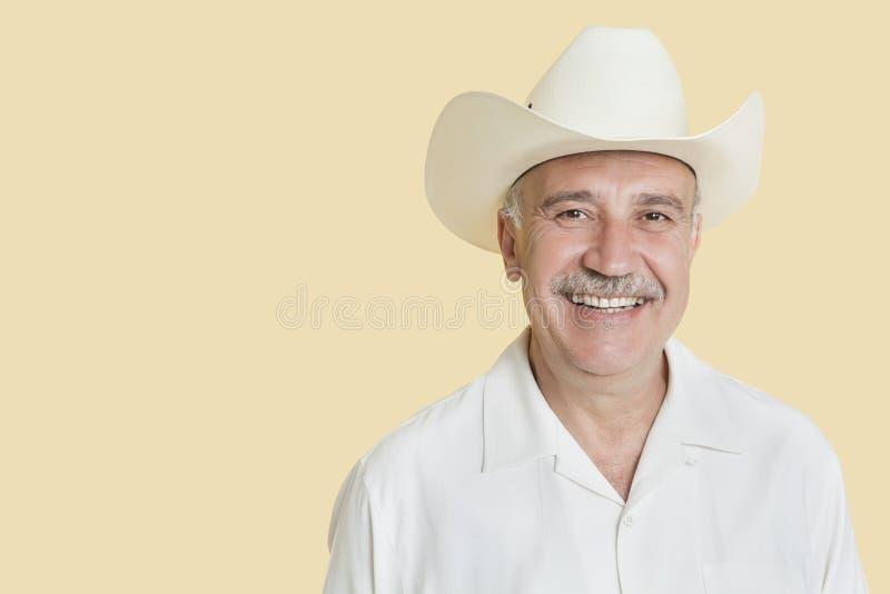 Stående av den lyckliga bärande cowboyhatten för hög man över gul bakgrund fotografering för bildbyråer