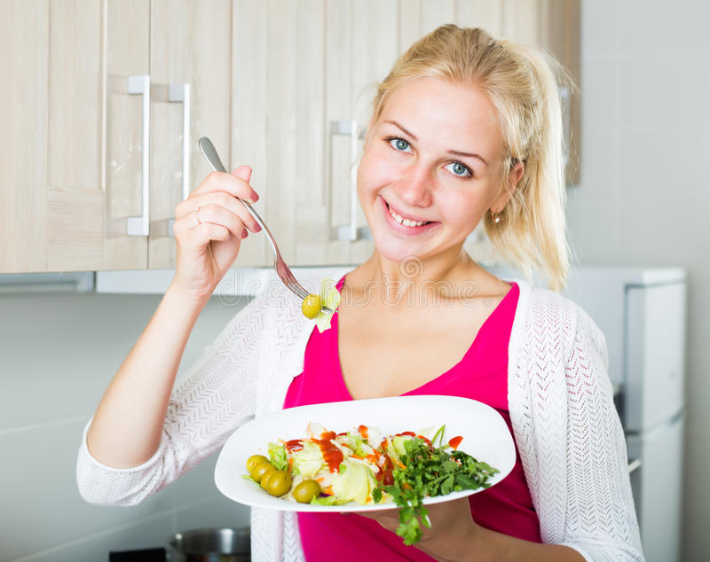 Stående av den lyckliga blonda flickan som äter sallad arkivbilder