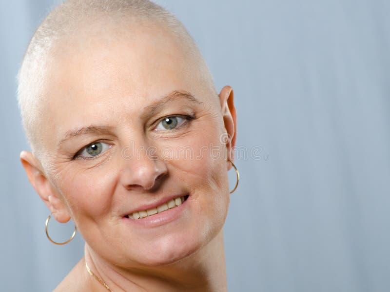 Stående av den lyckliga canceröverlevanden i studio efter lyckad kemoterapi royaltyfri foto