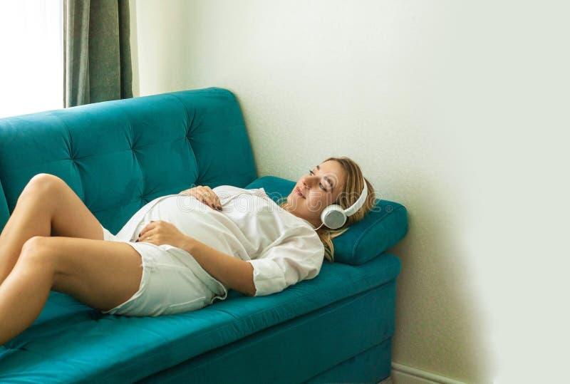 Stående av den lyckliga Caucasian blonda gravida kvinnan med headphonen royaltyfria bilder