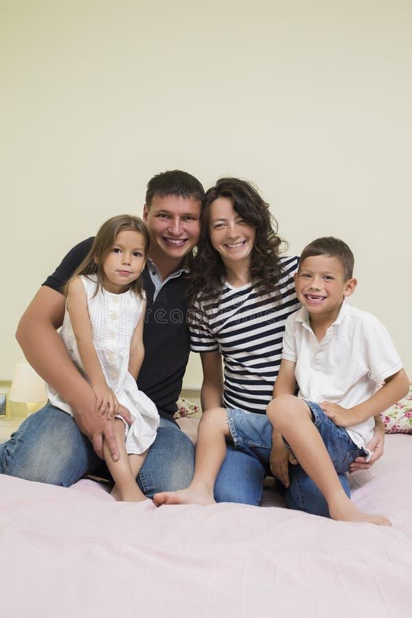 Stående av den lyckliga Caucasian familjen med två ungar som tillsammans poserar fotografering för bildbyråer