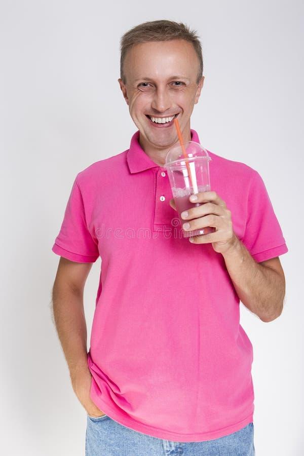 Stående av den lyckliga Caucasian mannen med smoothien mot vit arkivbilder