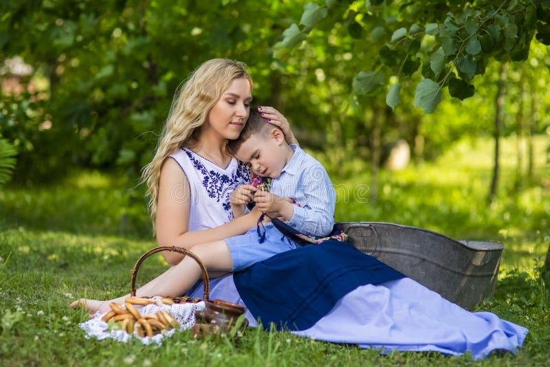 Stående av den lyckliga Caucasian modern med hennes upprivna lilla unge Posera med korgen som är full av brödcirklar utomhus royaltyfria bilder