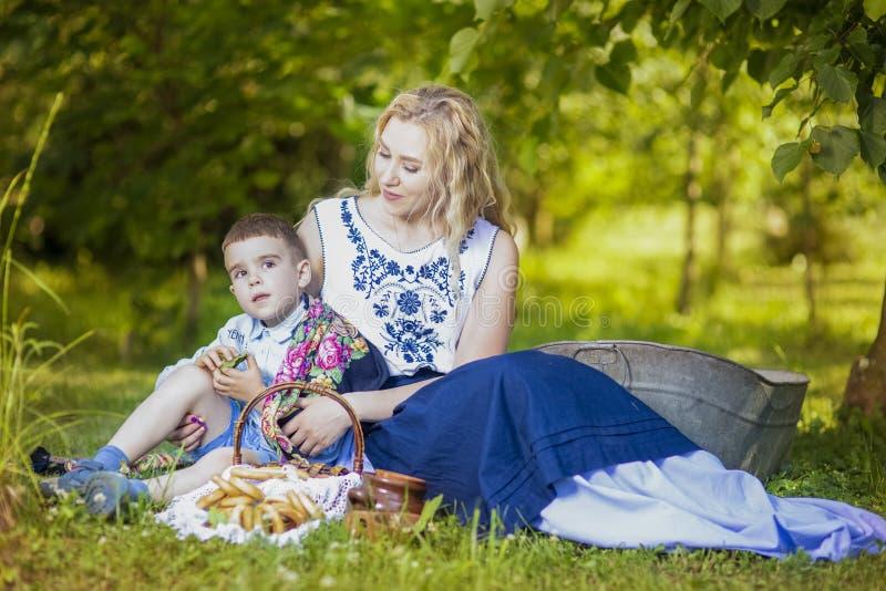 Stående av den lyckliga Caucasian modern och hennes lilla unge Posera med korgen som är full av brödcirklar utomhus arkivfoto