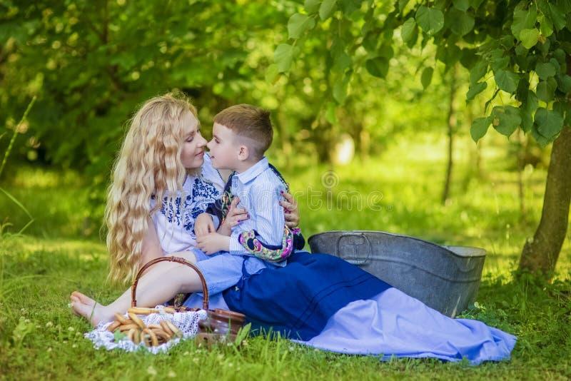 Stående av den lyckliga Caucasian modern som kysser hennes lilla unge Posera med korgen som är full av brödcirklar utomhus arkivfoto
