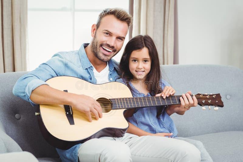 Stående av den lyckliga fadern som spelar gitarren med dottern fotografering för bildbyråer