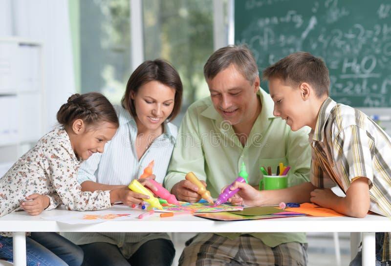 Stående av den lyckliga familjen av fyra som tillsammans hemma drar arkivbild