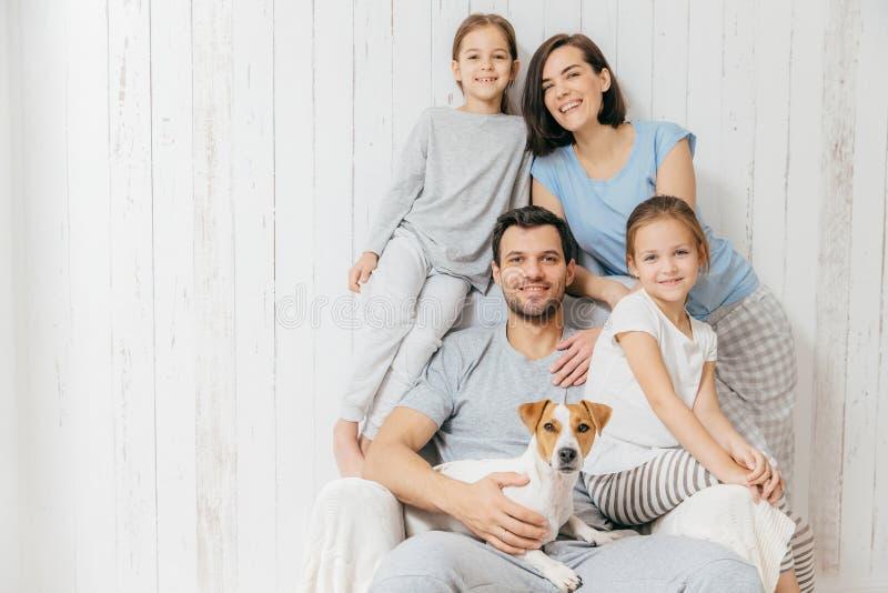 Stående av den lyckliga familjen inomhus Den stiliga fadern rymmer hunden, friare arkivbild