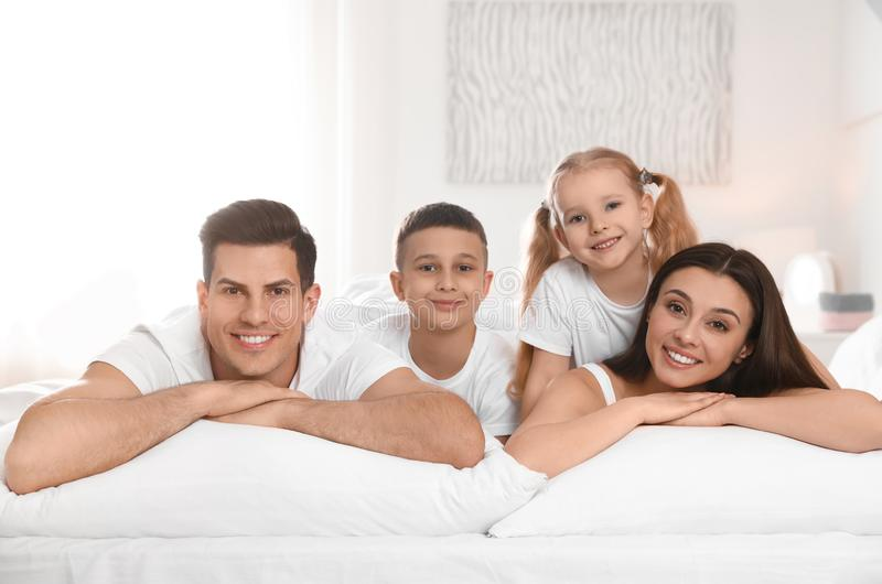 Stående av den lyckliga familjen på stor säng royaltyfri fotografi