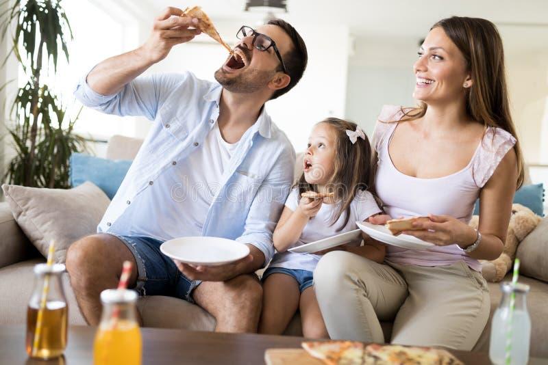 Stående av den lyckliga familjen som hemma delar pizza royaltyfri bild