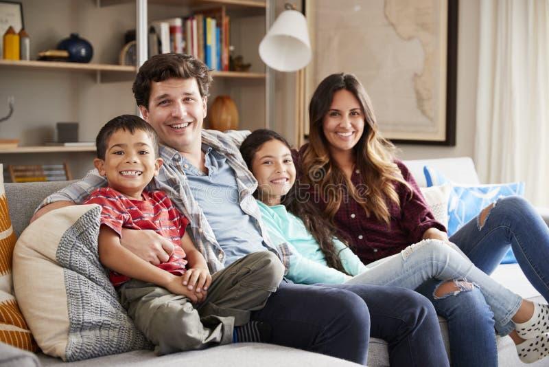 Stående av den lyckliga familjen som kopplar av på Sofa At Home Together arkivfoto