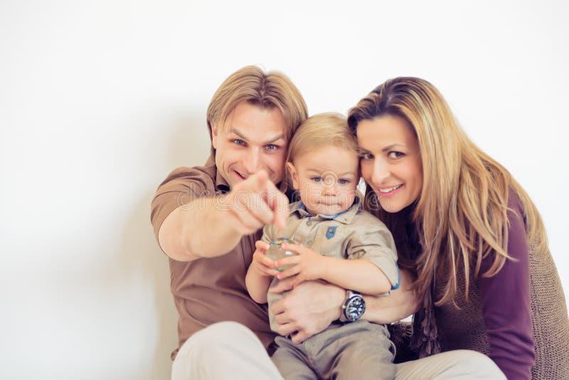 Stående av den lyckliga familjen som sitter på golvet och le Peka för finger royaltyfria foton