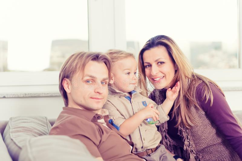 Stående av den lyckliga familjen som sitter på soffan och le royaltyfria foton
