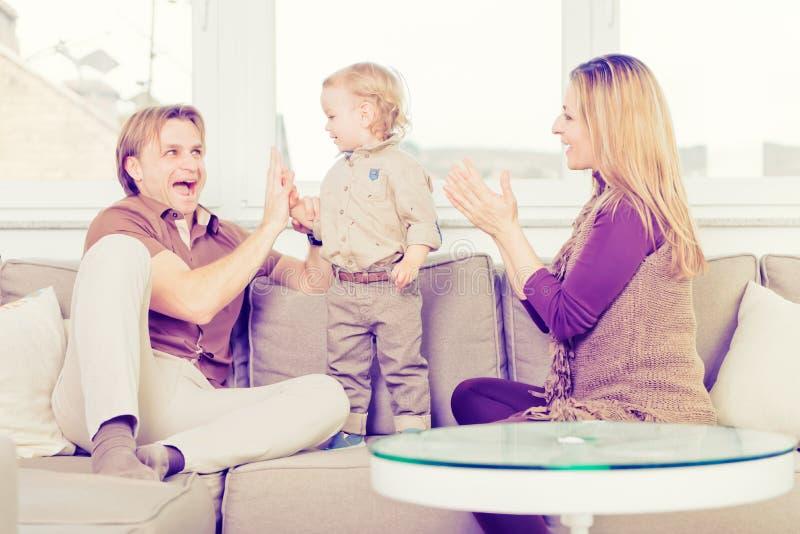 Stående av den lyckliga familjen som sitter på soffan och spela royaltyfri foto