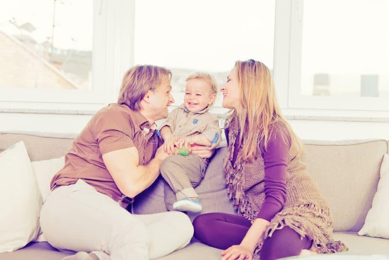 Stående av den lyckliga familjen som sitter på soffan och spela arkivfoto