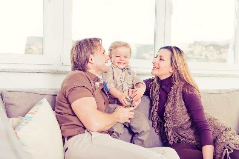 Stående av den lyckliga familjen som sitter på soffan och spela arkivfoton