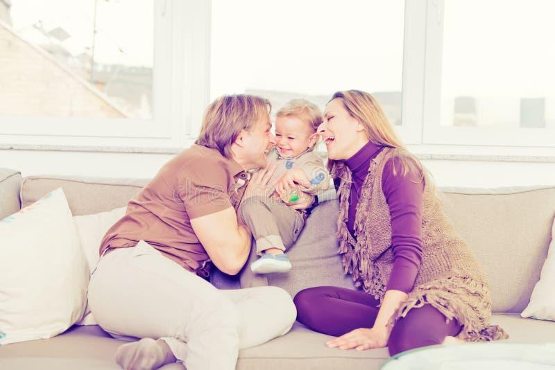Stående av den lyckliga familjen som sitter på soffan och spela arkivbild