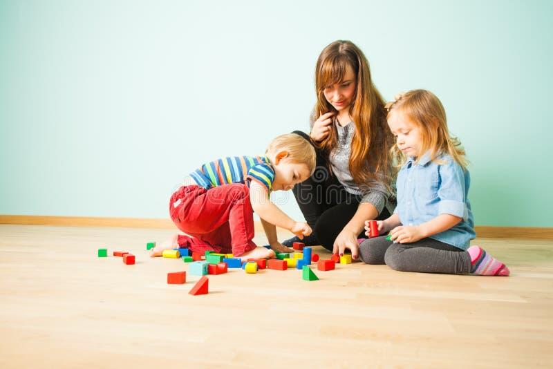 Stående av den lyckliga familjen som tillsammans inomhus spelar arkivbild