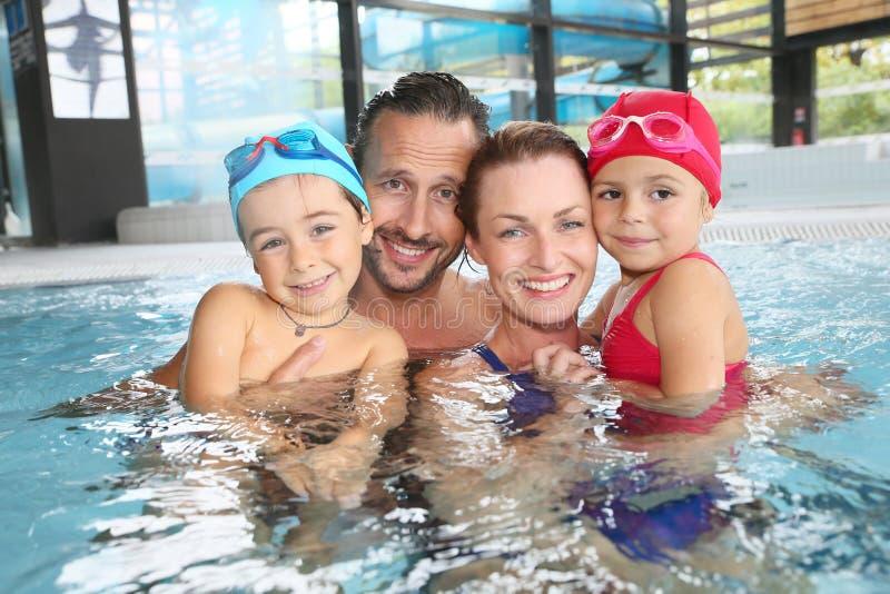 Stående av den lyckliga familjen som tycker om i simbassäng arkivfoto