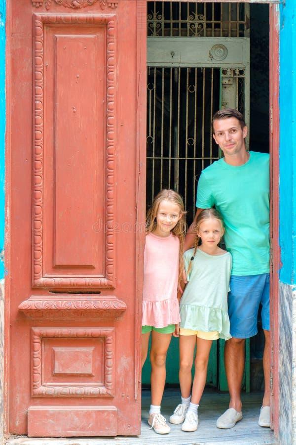 Stående av den lyckliga familjen som ut ser dörren på gamla lägenheter i havannacigarr arkivbild