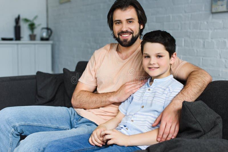 stående av den lyckliga familjen som vilar på soffan royaltyfria foton