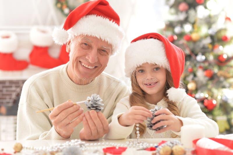 Stående av den lyckliga farfadern och barnet i jultomtenhattar royaltyfria foton