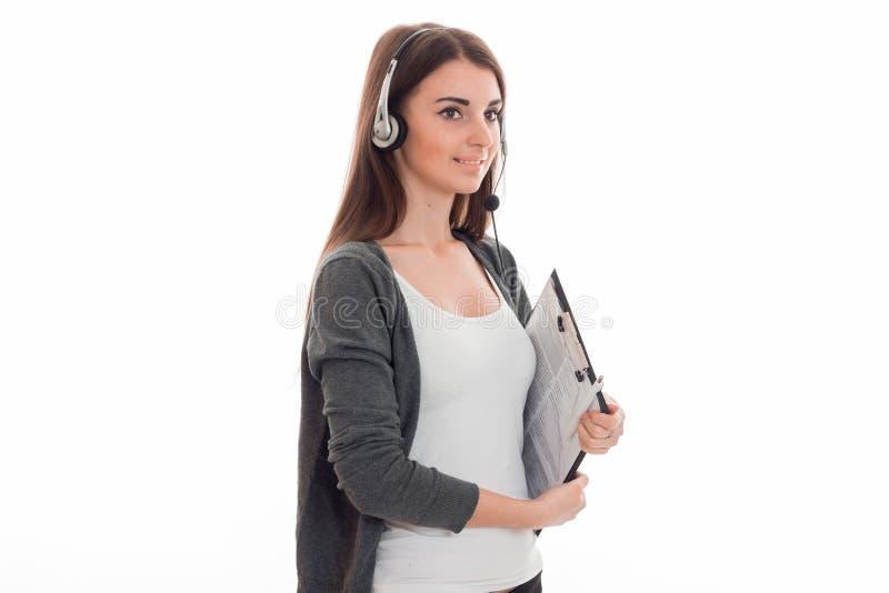 Stående av den lyckliga flickan för arbetare för brunettappellmitt med hörlurar och mikrofonen som isoleras på vit bakgrund royaltyfria bilder