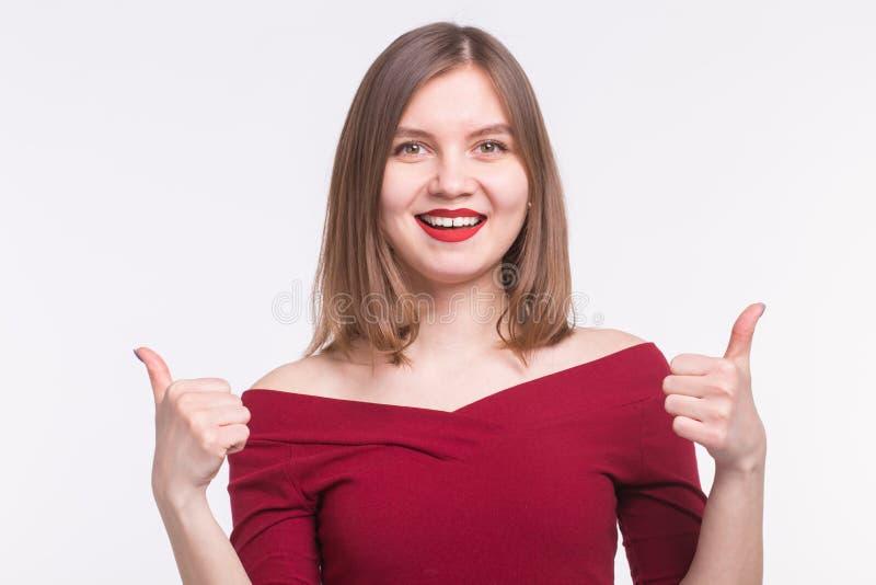 Stående av den lyckliga flickan med röda kanter och tummar upp på vit bakgrund arkivfoton