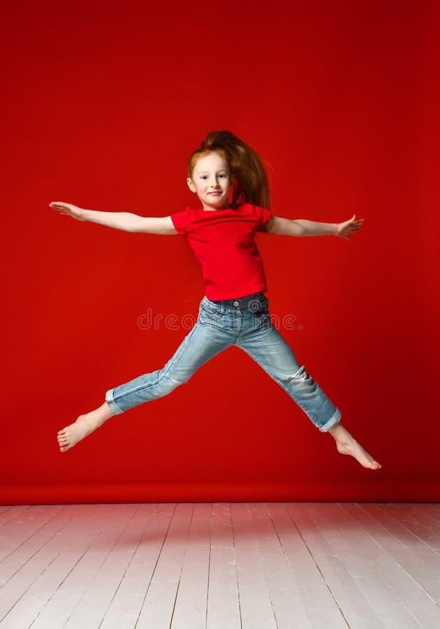 Stående av den lyckliga flickan som hoppar upp höga lyftande händer som isoleras på röd bakgrund arkivfoton
