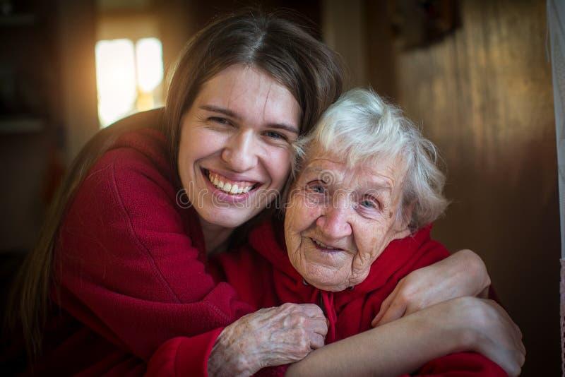 Stående av den lyckliga flickan som kramar hennes farmor arkivbild