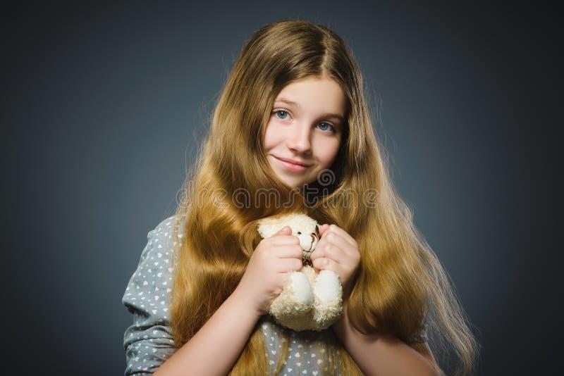 Stående av den lyckliga flickan som spelar med nallebjörnen som isoleras på grå färger royaltyfri bild