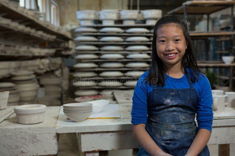 Stående av den lyckliga flickan som står near worktop royaltyfri foto